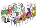 Das Bild zeigt mehrere Menschen, die gemeinsam an einem Tisch sitzen und mit Handzeichen abstimmen.