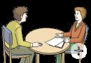 Das Bild zeigt zwei Frauen, die an einem Tisch sitzen. Eine Frau hat Papiere vor sich liegen und zeigt darauf.