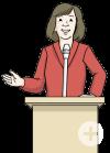 Das Bild zeigt eine Frau an einem Rednerpult. Sie spricht in ein Mikrofon.